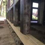 Neue Schwelle, die auf Keilen aufgebockt ist. Darunter altes Fundament.